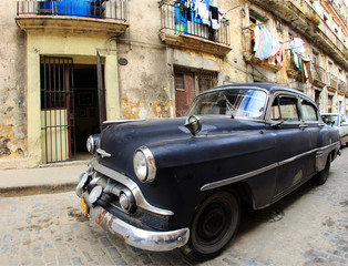 Garden Poster Cars from Cuba A classic old car is black color parked in front of the building