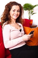 junge Frau mit Smartphone im Wohnzimmer