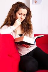 junge Frau auf Sofa sitzend, in ein Buch vertieft