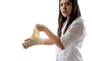 Teen girl wrapping her hand with a bandage isolated on white.