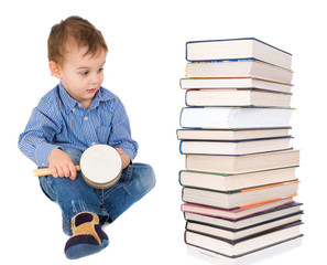 little boy sitting next to stacks of books