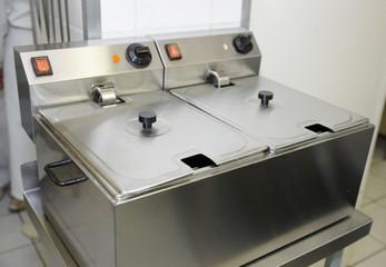 Clean deep fryer on restaurant kitchen