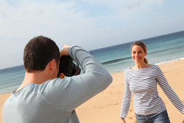 Man taking picture of girlfriend at the beach