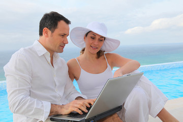 Couple using laptop computer by swimming-pool