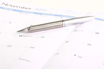 aufgeschlagener Kalender mit Stift Sommeranfang