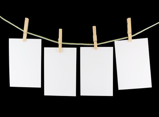 Blank pieces of paper and wooden clothespins isolated on black
