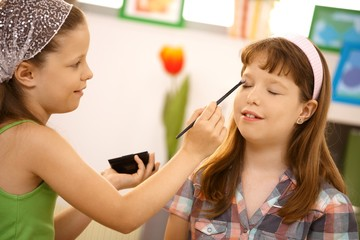 Young girl putting makeup on friend