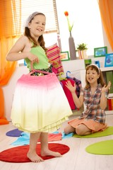 Young girls playing at home fitting dresses