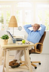 Portrait of cheerful old man in his study