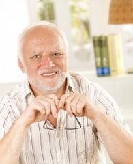 Portrait of senior man holding glasses