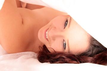 Frau liegt lachend unter der Bettdecke