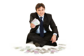 Successful businessman sitting on floor surrounded by money