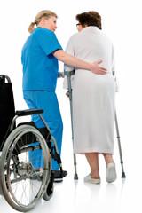 nurse helps a senior woman on crutches in hospital