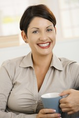 Portrait of happy woman drinking coffee