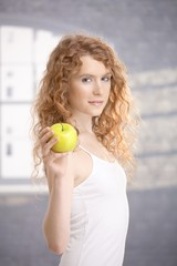 Pretty girl after workout holding apple in hand