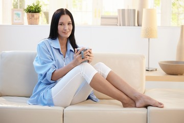 Portrait of smiling woman having coffee on sofa