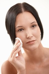 Closeup portrait of young woman cleaning face