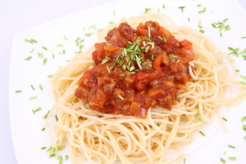 Spaghetti bolognese on a plate decorated with some chives