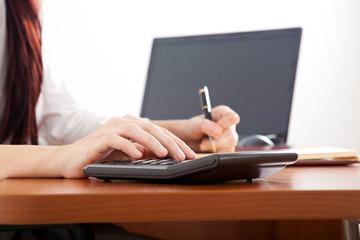 Businesswoman using calculator in her office