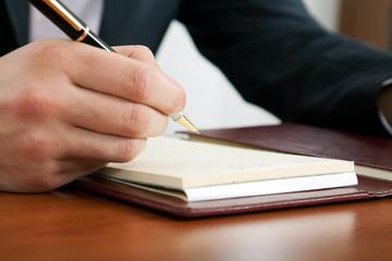 Businessman writing on agenda