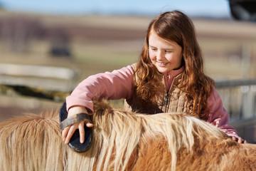 mädchen striegelt pferd