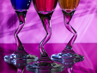 Curved stems of three glasses of liqueur on pink background