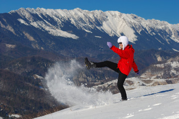 Happy girl shooting the snow in a fine day in Mountains