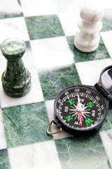compass on a chess board and chess pieces