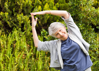 Mature woman doing her streches in the garden