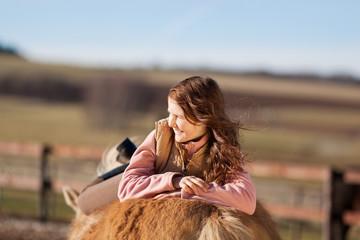 junges mädchen entspannt auf pferderücken