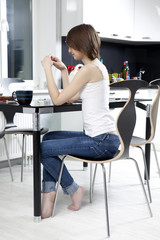 young woman drinking tea with lemons in kitchen at home