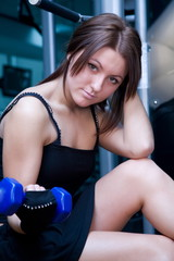 Girl with dumbbells in the gym.