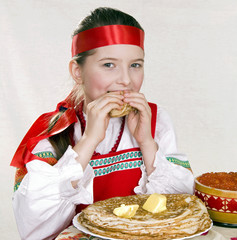 Russian  girl  behind a table with pancakes