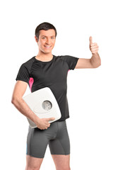 Happy athlete holding a weight scale and giving thumb up