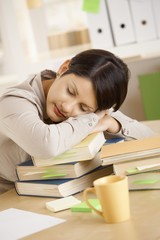 Tired student resting on pile of books