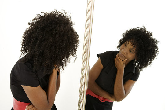 Lady looking at herself in mirror with quizzical expression