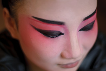 a chinese opera actress is painting her face backstage