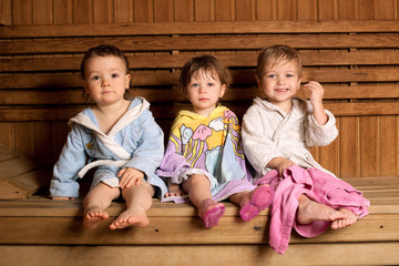 three funny children sitting in sauna