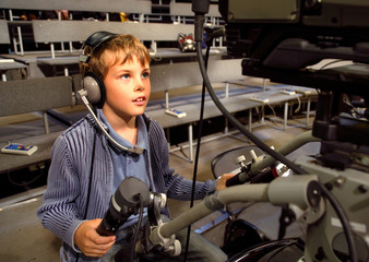 Little boy with headphones and microphone sits on camera