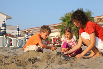 Mother with two children sits on  beach in  day-time
