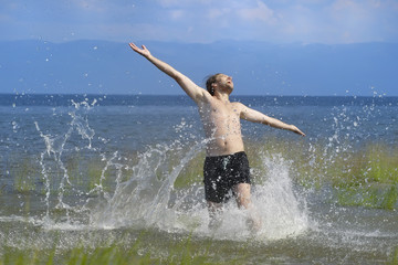 young man running along the water