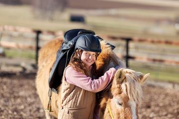 mädchen mit reitkappe und pferd