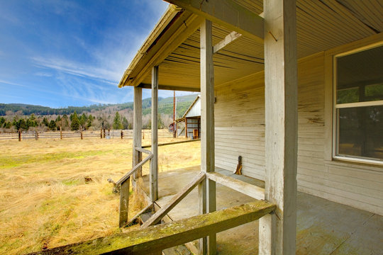 Grey old rustic hosue with porch and the view of the farm land