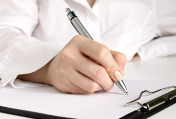 hand with pen writing on the white page in clipboard