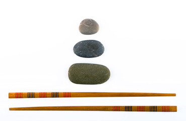 chopsticks and stones isolated on white background
