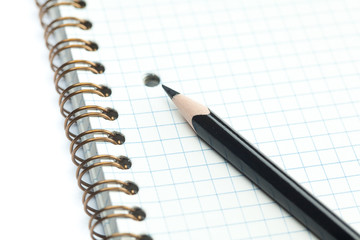 plaid notebook with a spiral  and pencil