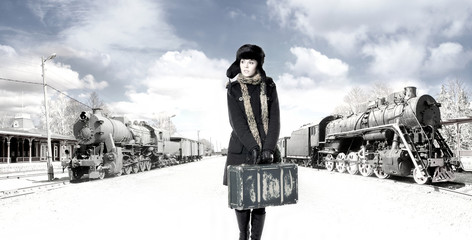 A young woman walkin on an old train station background