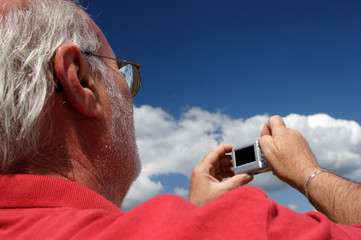 Senior man in a red shirt using a compact digital camera