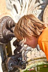 Boy is drinking water on a public fountain
