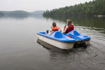 Mother and daughter pladdleboating on a lake